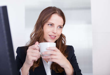 Smiling attractive businesswoman drinking a cup of tea or coffee while seated at her desk taking notes Stock Photo - 15175367