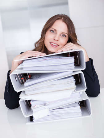 hardworking: Overworked stressed businesswoman resting her chin on the top of a  high stack of files as she sits at her desk