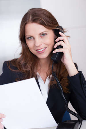 verbal: Businesswoman talking on the handset of a telephone as she sits at her desk working Stock Photo