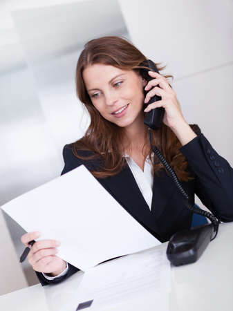 verbal communication: Businesswoman talking on the handset of a telephone as she sits at her desk working Stock Photo