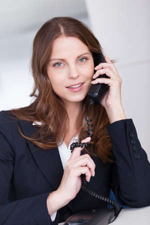 executive assistants: Businesswoman talking on the handset of a telephone as she sits at her desk working Stock Photo
