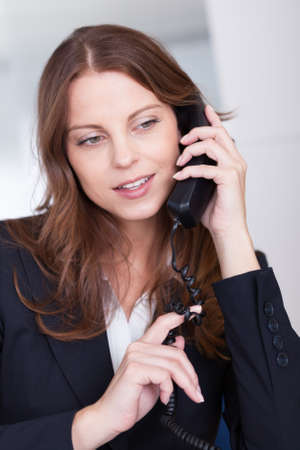 Businesswoman talking on the handset of a telephone as she sits at her desk working photo