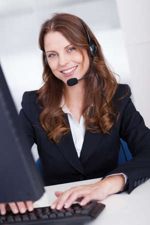 Smiling receptionist or call centre worker sitting typing at a computer while speaking into a headset with a microphone photo