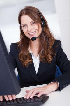 secretaria: Sonriente recepcionista o call center escribir trabajador sentado frente a una computadora mientras habla por el auricular con un micrófono