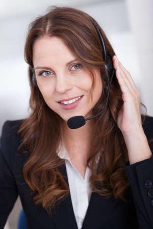 secretaria sexy: Sonriente recepcionista o call center escribir trabajador sentado frente a una computadora mientras habla por el auricular con un micr�fono