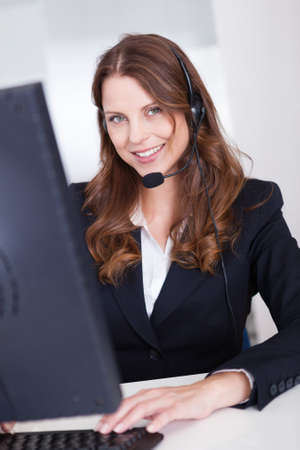 Smiling receptionist or call centre worker sitting typing at a computer while speaking into a headset with a microphone Stock Photo - 15175509