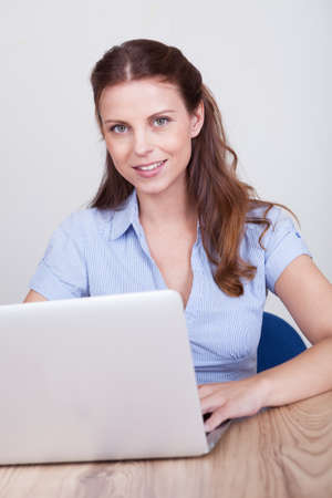 Friendly smiling woman sitting at a wooden table working at a laptop Stock Photo - 15175608