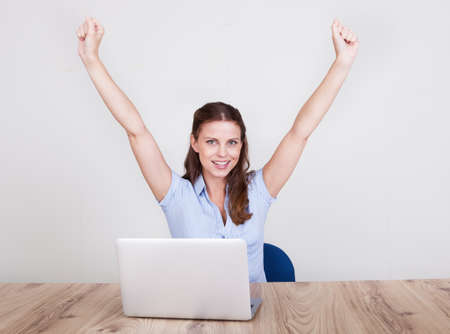 jubilation: Upbeat successful young woman sitting at her laptop making a fist of jubilation and celebration