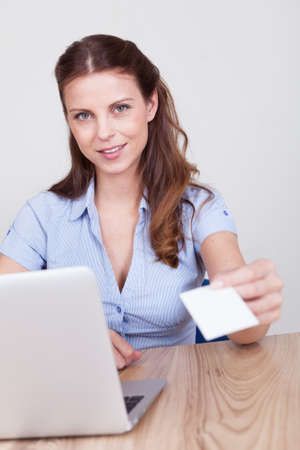 Young businesswoman sitting behind her laptop holds out her hand offering her card with focus to her face Stock Photo - 15175541