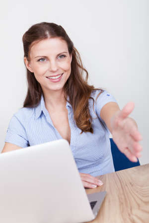 conclude: Young woman seated at a table offering to shake hands in welcome or in order to seal a business deal or transaction Stock Photo