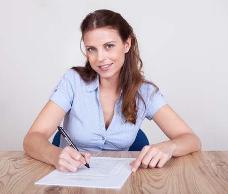 secretaria sexy: Mujer sentada escribiendo en una hoja de papel en una mesa de madera con el grano distintivo Foto de archivo