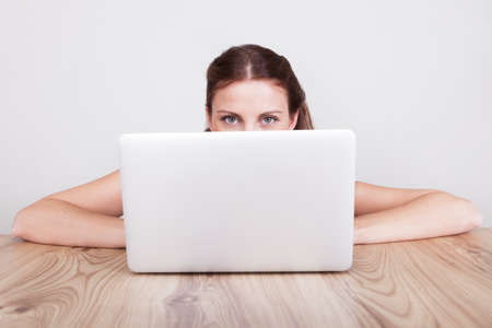 Low angle view across a wooden table of a young woman hiding behind her laptop Stock Photo - 15175510