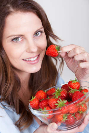 sexy food: Smiling young woman enjoying a bowl of fresh ripe red juicy whole strawberries which she is eating as a snack