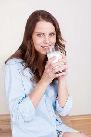 cradling: Smiling longhaired brunette woman drinking a glass of fresh milk sitting indoors