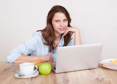 apple computer: Woman sitting at her desk working on her laptop
