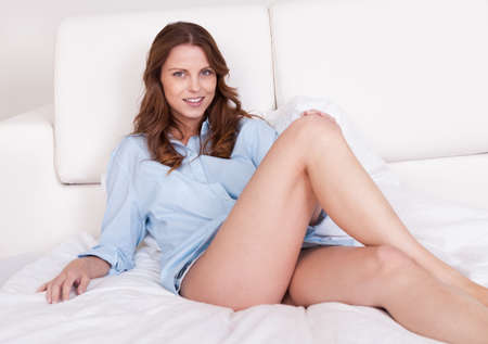 shapely legs: Sexy young woman in a casual shirt with shapely long legs relaxing on a bed Stock Photo