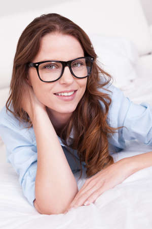 Attractive young woman wearing glasses lying on her stomach relaxing on her bed Stock Photo - 15175623