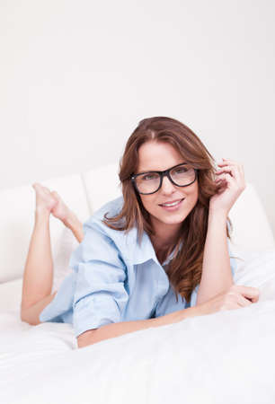 Attractive young woman wearing glasses lying on her stomach relaxing on her bed Stock Photo - 15175663