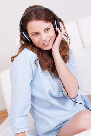 Woman relaxing on her bed in a casual blue shirt wearing stereo headphones bed listening to music Stock Photo - 15175388