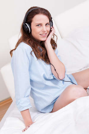 Woman relaxing on her bed in a casual blue shirt wearing stereo headphones bed listening to music Stock Photo - 15175387