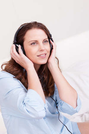 Woman relaxing on her bed in a casual blue shirt wearing stereo headphones bed listening to music Stock Photo - 15175374