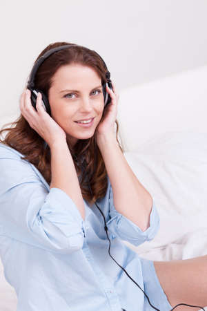 Woman relaxing on her bed in a casual blue shirt wearing stereo headphones bed listening to music Stock Photo - 15175428