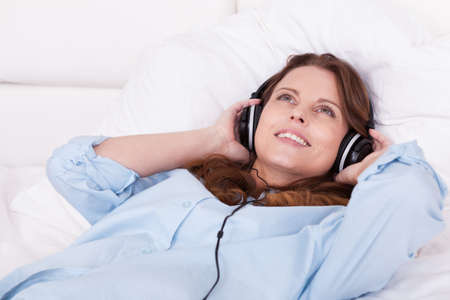 Woman relaxing on her bed in a casual blue shirt wearing stereo headphones bed listening to music Stock Photo - 15175677