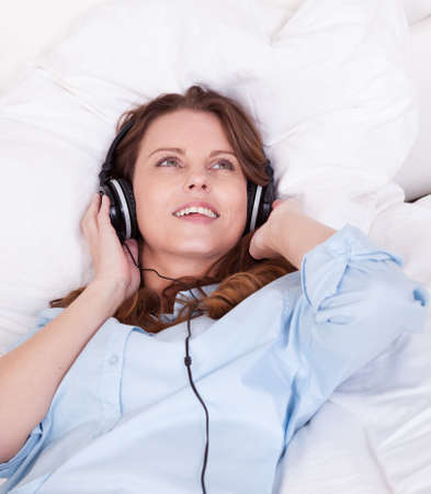 Woman relaxing on her bed in a casual blue shirt wearing stereo headphones bed listening to music Stock Photo - 15175466