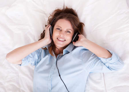 Woman relaxing on her bed in a casual blue shirt wearing stereo headphones bed listening to music Stock Photo - 15175667