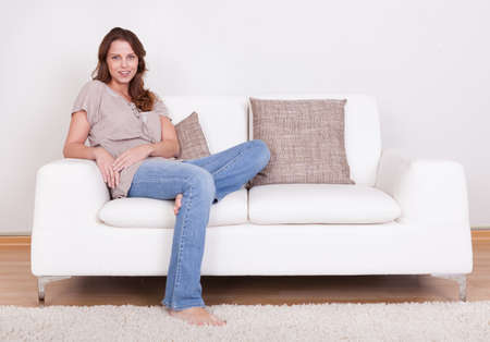 lounging: Casual barefoot woman in jeans sitting on a couch in her living room with a cheerful smile Stock Photo