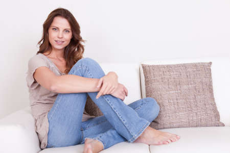 seating furniture: Casual barefoot woman in jeans sitting on a couch in her living room with a cheerful smile Stock Photo