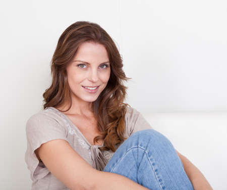 unwinding: Casual barefoot woman in jeans sitting on a couch in her living room with a cheerful smile Stock Photo