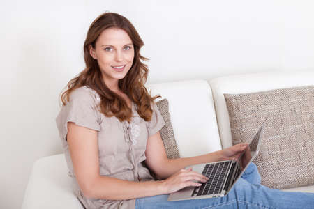 unwinding: Casual barefoot woman relaxing on a sofa using her laptop