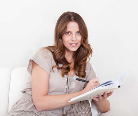 handholding: Pretty young woman sitting on a couch writing notes in a notebook or diary that she is handholding Stock Photo