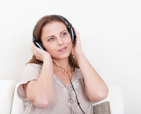 Smiling woman wearing stereo headphones sitting listening to music with her hands over the earphones photo