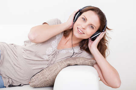 pastimes: Smiling woman wearing stereo headphones sitting listening to music with her hands over the earphones