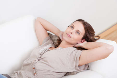 unwinding: Casual barefoot woman in jeans lying on a couch in her living room with a cheerful smile Stock Photo