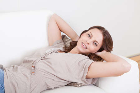 contented: Casual barefoot woman in jeans lying on a couch in her living room with a cheerful smile Stock Photo