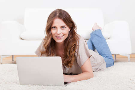 Portrait of an attractive young female sitting on the carpet using a laptop photo