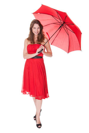 Beautiful elegant woman in a trendy red dress posing under an open red umbrella isolated on white photo