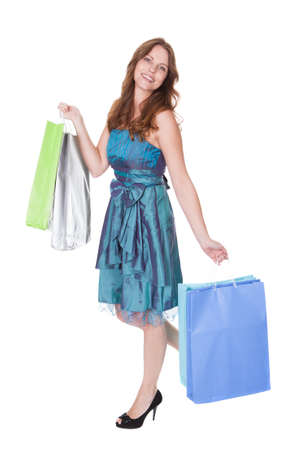 spendthrift: Beautiful happy fashionable shopper returning from a spending spree with a satisfied smile and hands full of shopping bags