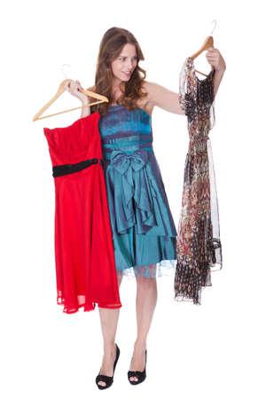 cocktaildress: Mooie brunette fashion model met een keuze van jurken die ze omhoog houdt op hangers geïsoleerd op wit