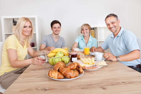 Happy family with two teenage children sitting around the table enjoying a healthy breakfast Stock Photo - 15225919