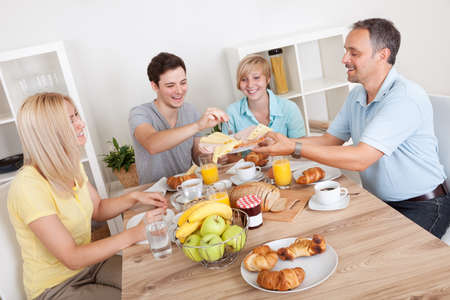 prepared food: Happy family with two teenage children sitting around the table enjoying a healthy breakfast Stock Photo