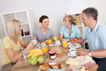 Happy family with two teenage children sitting around the table enjoying a healthy breakfast photo