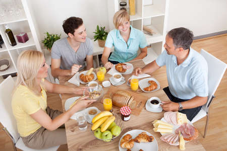 mealtime: Happy family with two teenage children sitting around the table enjoying a healthy breakfast Stock Photo