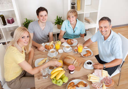 topdown: Happy family with two teenage children sitting around the table enjoying a healthy breakfast Stock Photo