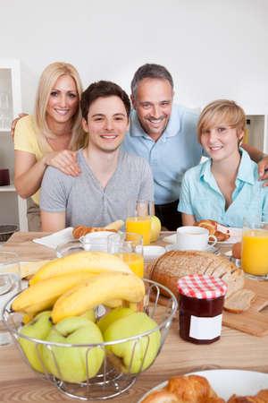 Familia feliz con dos hijos adolescentes que se sientan alrededor de la mesa disfrutando de un desayuno saludable