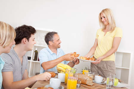 Young healthy family seated at the table being served croissants for breakfast by the smiling mother Stock Photo