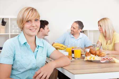 Attractive teenage girl sitting in the foreground with her family seated at the table in front of a large healthy breakfast Imagens